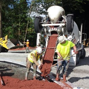 Two Custom Concrete employees pour red-tinted concrete into a form for a new traffic roundabout.