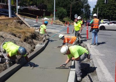 Concrete finishing crew installing new sidewalks in public spaces