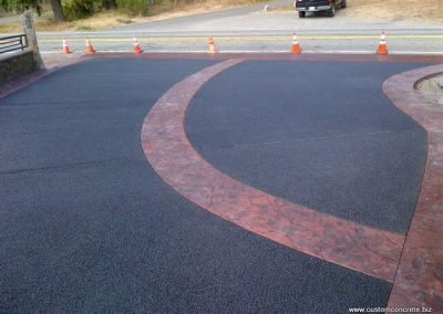 Black pervious concrete driveway with colored and stamped bands