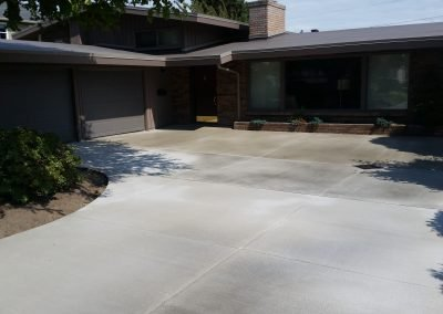 Broom-finished concrete driveway tucks neatly against existing landscaping and brickwork.