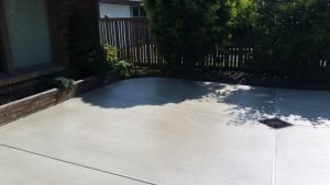 Concrete driveway slopes to drain and tucks neatly against brick planters and landscaping.