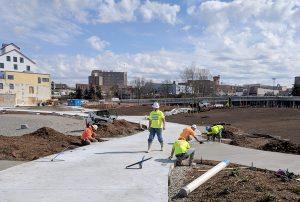 Concrete workers from Custom Concrete perform various sidewalk installation tasks at Waypoint Park in Bellingham, Washington.